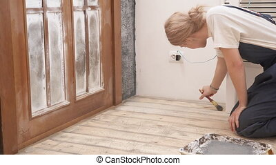 Woman painter in uniform colors the floor in apartment.