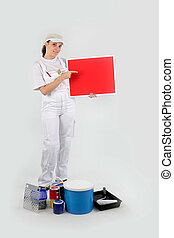 Woman painter showing red cardboard