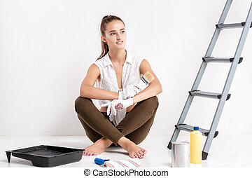 woman painting a wall in house - beautiful attractive woman...