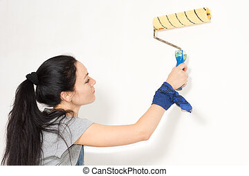 Woman painting a wall with a roller
