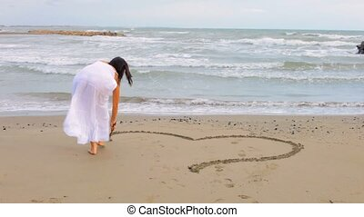 Woman painting heart on sand