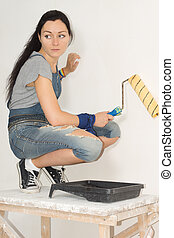 Woman painting her house with a roller