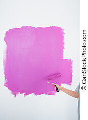 Woman painting her wall pink