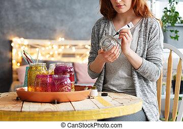 Woman painting jar at home