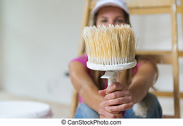 Woman painting the walls. - Happy smiling woman sitting on...