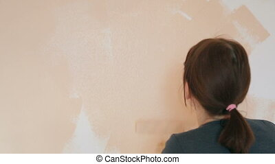 Woman painting wall in the room
