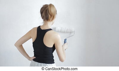 Woman painting wall in white
