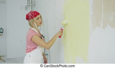 Woman painting wall with roller - Side view of beautiful...