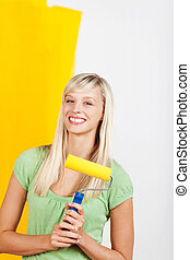 Woman painting wall yellow