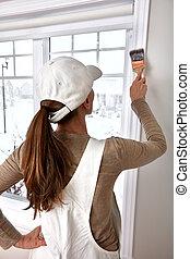 Woman painting window trim
