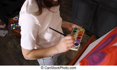 woman painting - woman artist painting with acrylic paint a...