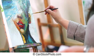 Woman paints a painting on canvas. Art academy or drawing...