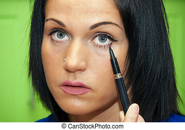 Woman paints her eyelashes