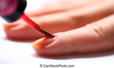 woman paints her nails with red lacquer