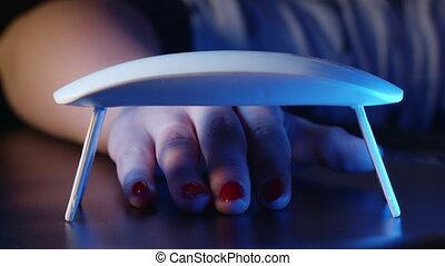 Woman paints nails with red gel polish at home alone. Uv led lamp for drying manicure. Modern method of working with hands. Ultraviolet instrument, master equipment. 4k.