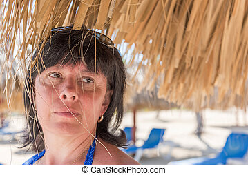 Woman palm beach umbrella - portrait of a middle-aged...