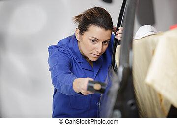 Woman panel beating vehicle bodywork
