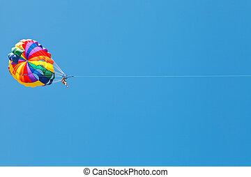 woman parakiting on parachute in blue sky