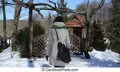 woman park gate winter - woman dressed in warm clothes walk...