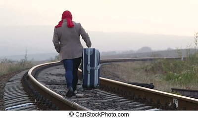 Woman passenger with luggage walking along train track