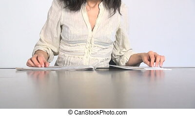 woman passing pages of newspaper