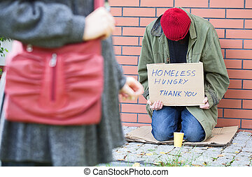 Woman passing poor man - Woman passing poor homeless and...