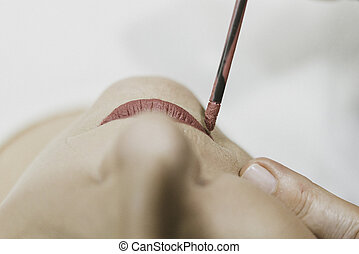 Woman passing red lipstick in beauty salon