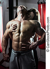 Woman passionately embraces muscular man in the gym....