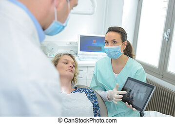 woman patient at dental surgery point teeth xray tablet dentist