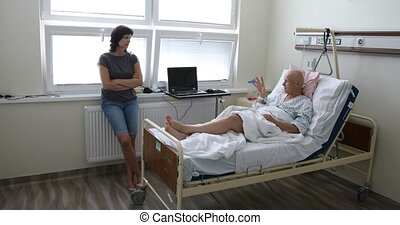 woman patient with cancer in hospital with friend - middle ...