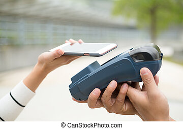 Woman pay with mobile phone on pos machine