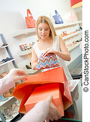 Woman paying at the till in a clothes shop