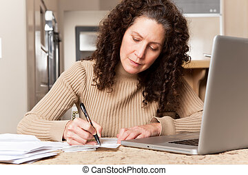 Woman paying bills - A shot of a middle age caucasian woman...