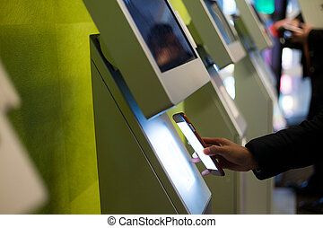 Woman paying by cellphone on ticketing machine