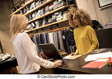 Woman paying female sales assistant with credit card in clothes shop