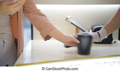 Woman paying for coffee using modern expensive smart phone...