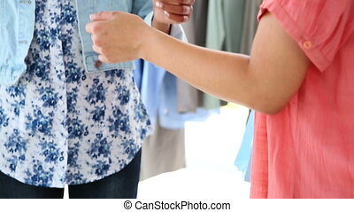 Woman paying for her purchases with credit card in a...