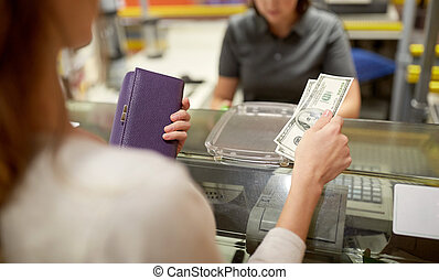 woman paying money at store cash register