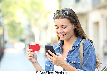 Woman paying online with a credit card outdoors