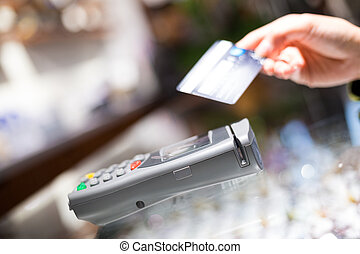 Woman paying with NFC technology on credit card,