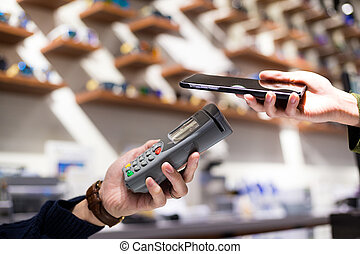 Woman paying with NFC technology on mobile phone