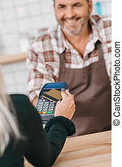 woman paying with pos terminal at cafe