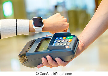 Woman paying with smartwatch by NFC