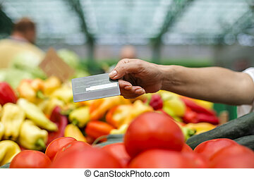 Woman pays with credit card at a market
