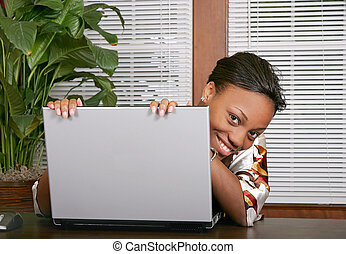 woman peeking around laptop - African American female adult ...