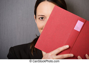 Woman peeking out from behind a book