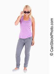 Woman peeking over her sunglasses