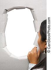Woman peeking through hole in wall