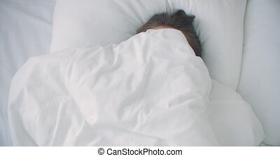 woman Peeking under duvet and smiling. . High quality 4k footage