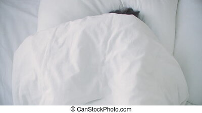 woman Peeking under duvet and smiling. Smiling cheerful woman peeking out from under the blanket in bed at home and kissing camera. High quality 4k footage